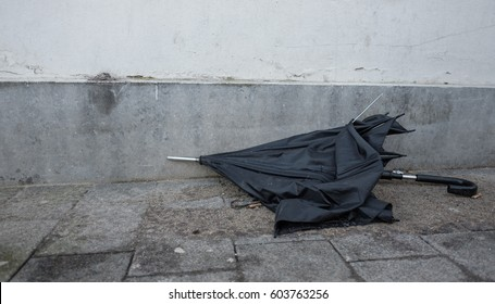 broken black umbrella is thrown away as garbage and lies abandoned on the streets