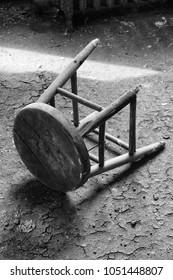 broken black and white stool against textured floor