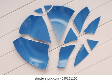 broken blue plate is on table, broken-down dish, crushed tableware is on white background,