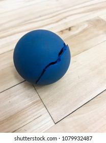 A broken blue racquetball on a wooden court floor