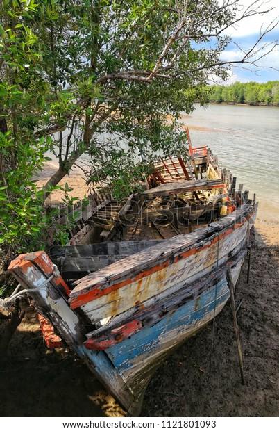Broken boat beside river