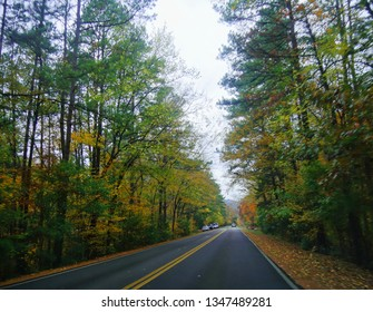BROKEN BOW, OKLAHOMA—OCTOBER 2017: Straight concrete road with cars parked on the roadside with full autumn colors at the Beavers Bend State Park in Broken Bow, southeastern part Oklahoma.