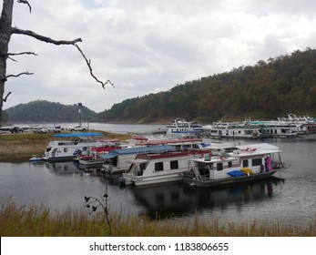 BROKEN BOW, OKLAHOMA—OCTOBER 217: Row of colorful boats and yachts docked at the Beavers Bend State Park marina on a beautiful autumn day at the Broken Bow Lake in Oklahoma, with a dead tree trunk on