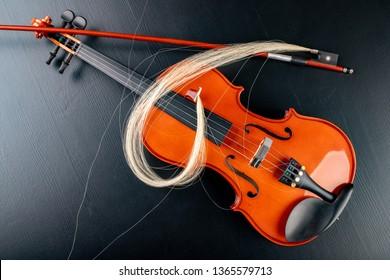 Broken bow to the violin. Damaged musical instrument. Dark background.