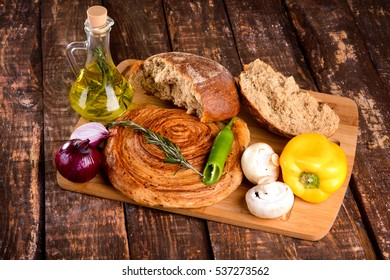 the broken bread on the Board next to olive oil and vegetables on wooden table