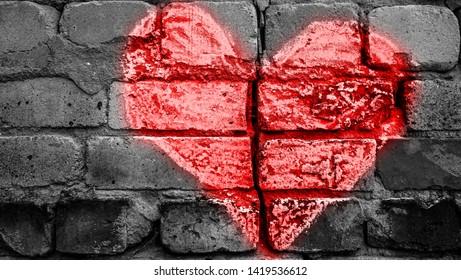 Broken brick wall with chalk drawing of red  heart. divorce, treachery concept