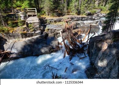 Broken bridge across the waterfall. Taken in Numa Falls, Kootenay National Park, British Columbia, Canada.