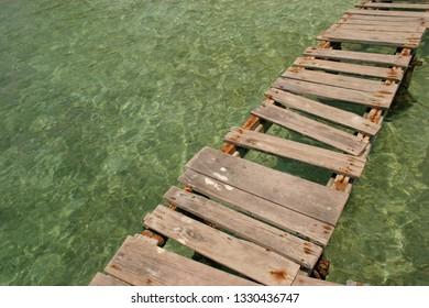 A broken bridge over crystalline water