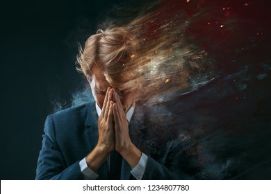 broken businessman. Stress at work, concept. man in a business suit grabbed his head and sprayed into pieces. dark background
