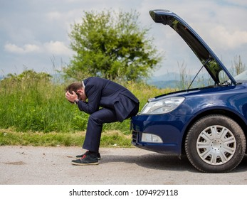 A broken car on the road, the driver is holding his head, an open hood, a car in failure