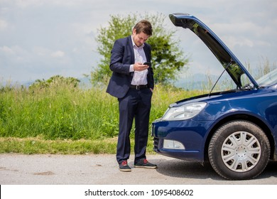 A broken car on the road, the driver holds an open hood and watches what has broken down, a roadside assistance is waiting