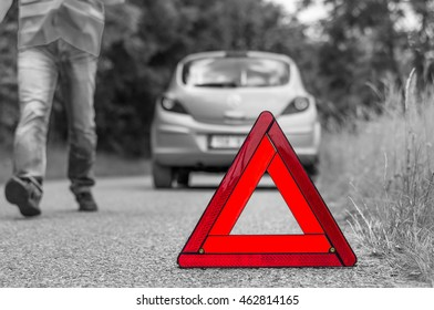 Broken car on the road and unhappy driver with red warning triangle - black and white concept