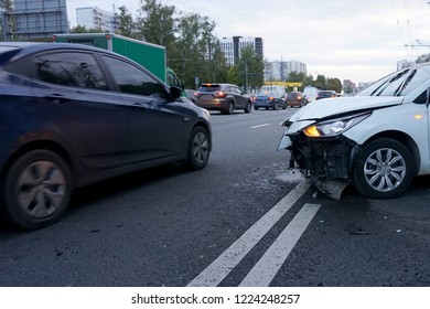 A broken car is standing on the road on which other cars are driving. The concept of careless driving a car.