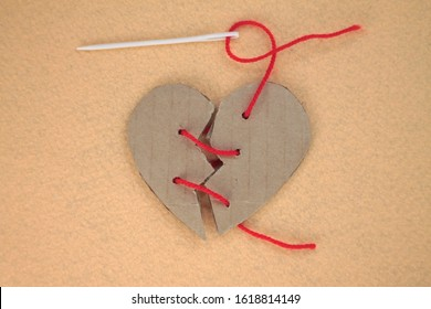 Broken cardboard heart on felt orange background. Two halves of the heart sewn together in red thread. The concept of a broken heart, unrequited love. Valentine's Day stock photo with empty space