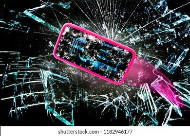Broken cell phone going through shards of glass.