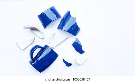 Broken ceramic blue cup on white background