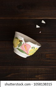 Broken Ceramic Bowl with Shard Pieces on Rustic Dark Wood Background with extra room or space for copy, text, words or design.  A vertical flatlay from above view