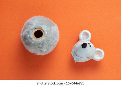 broken ceramic figure of a rat or mouse on an orange background. Head apart from the body