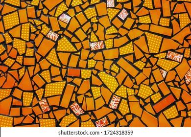 Broken ceramic tiles mosaic seamless tile-shard pattern background yellow orange colors