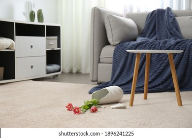 Broken ceramic vase on floor in room