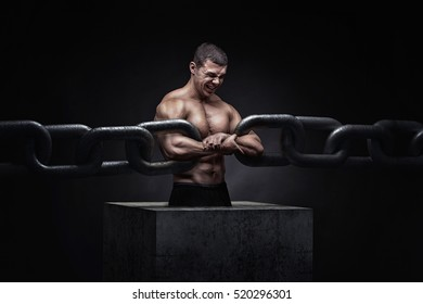 Broken Chain - Freedom Concept . Brutal man bodybuilder athlete holding a chain on a black background. metaphor
