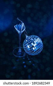 Broken champagne drinking glass with disco ball. New Year party, birthday, girls day or other celebration event. After party. Creative Minimal party concept. Black background. Festive bokeh