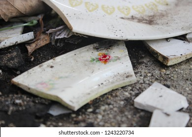 Broken china dishes in a pile of dirt in abandoned farmhouse