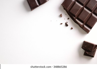 Broken chocolate bar isolated on white table. Horizontal composition. Top view