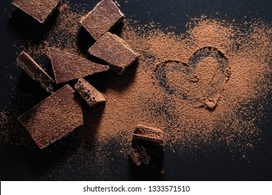 broken chocolate bar on a black background, cocoa powder painted heart