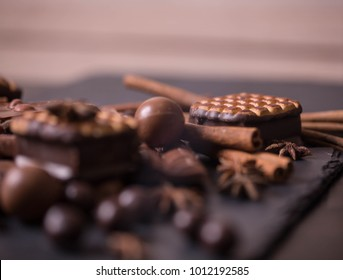 Broken chocolate bars and spices on wooden table/ nut chocolate / chocolate bar background/ Sweet food photo concept. Milk pieces with whole hazelnuts