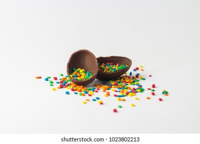 Broken Chocolate Easter egg into two halves with a colorful candy decorations on a white background. Easter concept.