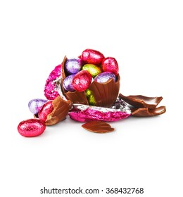 Broken chocolate easter egg wrapped in pink foil with colorful candies isolated on white background