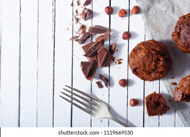 broken chocolate muffin and hazelnuts, fork on white wood table