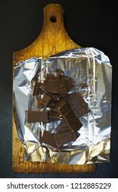 Broken chocolate on a wooden board. Overhead vertical shot