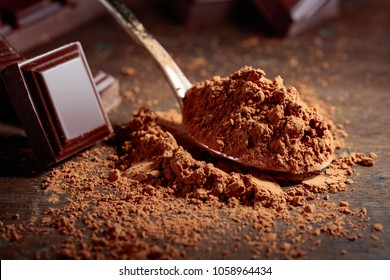 Broken  chocolate pieces and cocoa powder in small spoon on a wooden background.