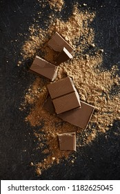 Broken chocolate pieces and cocoa powder on black. Chunks of chocolate onr dark stone background.