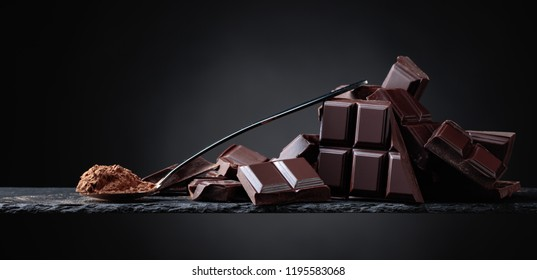 Broken chocolate pieces and cocoa powder in small spoon on a black background. Copy space .
