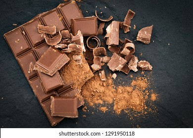 Broken chocolate pieces and cocoa powder on a dark background.
