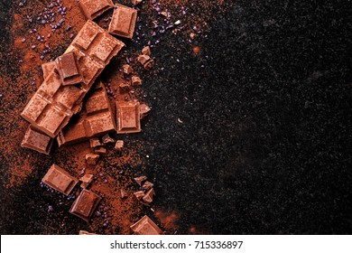 Broken chocolate pieces and cocoa powder on marble. The chunks of chocolate over dark background