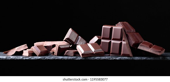 Broken chocolate pieces on a black background. Copy space.