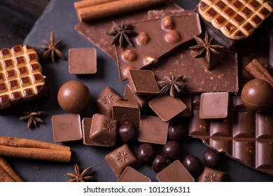 Broken chokolate bars and spices on a wooden table ansd shale/ dark and milk/  whole hazelnuts