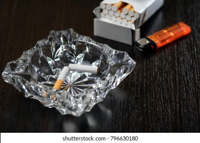 broken cigarette in ashtray in front of cigarette pack and lighter, stop smoking concept
