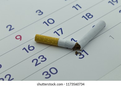A broken cigarette lies on the calendar. The concept is time to quit smoking. Place for inscription or text.