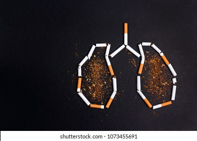 Broken cigarettes and tobacco in the form of lungs on black background. No smoking concept. Flat lay, top view, copy space.
