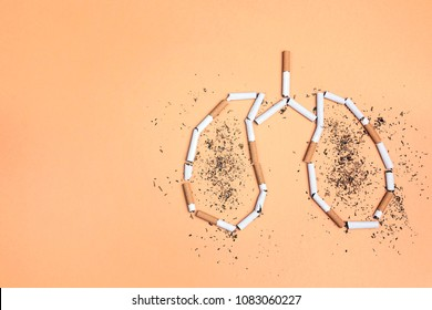Broken cigarettes and tobacco in the form of lungs on yellow background. No smoking concept.  Flat lay, top view with copy space.