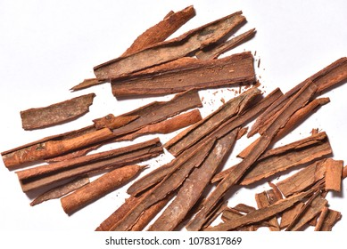 Broken cinnamon close-up on white background, sharp edges of cinnamon. Slivers of cinnamon