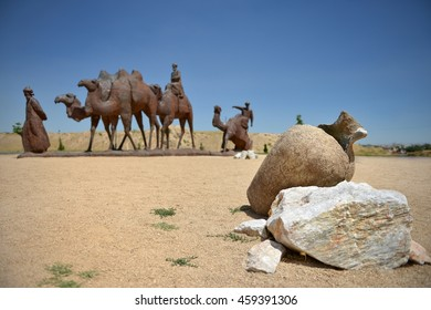 Broken clay pitcher without water. Caravan of camels in the desert.