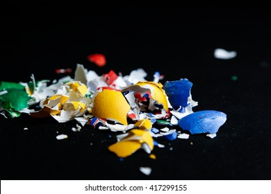 Broken colored egg shells on black background