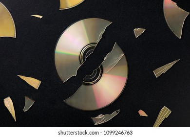 Broken Compact Disc with Pieces Scattared on Black Surface