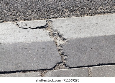 broken concrete curb near the roadway. photo close-up in the city
